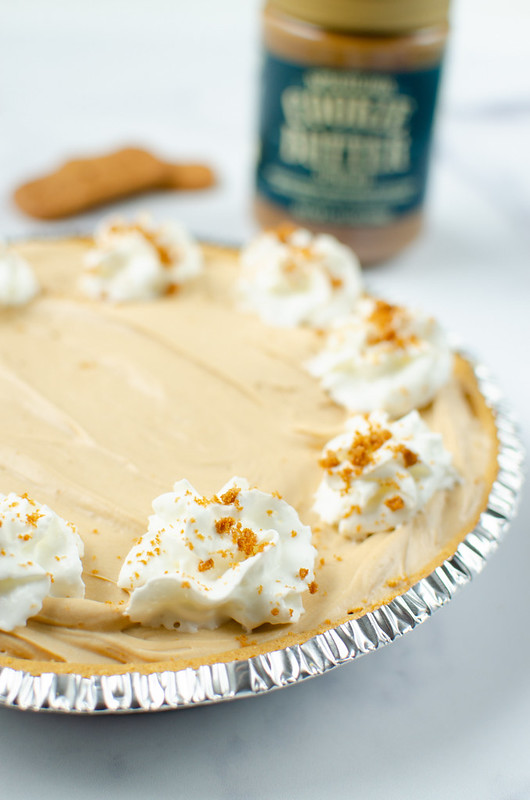 Cookie butter pie with whipped cream and crushed cookies on top; jar of cookie butter and 2 cookies in background