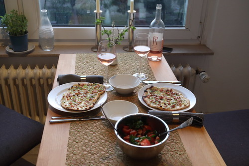 Flammkuchen mit Lauch und Speck sowie Tomaten-Rucola-Salat (Tischbild)
