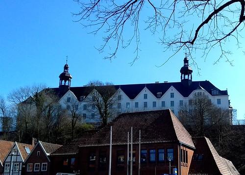 das weiße Plöner Schloss leuchtet über der Stadt - in Explore!