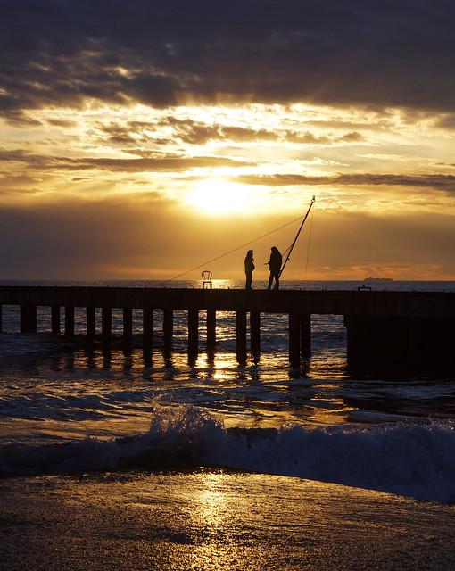 Fishers in a gold sunset at Cinquale di Montignoso