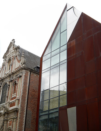 Brick wall of an old building next to a new building of glass and rust with the same triangular roof in Brussels, Belgium