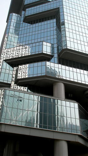 Interlocking geometric shapes in a highrise tower with reflections in the glass (Hong Kong)