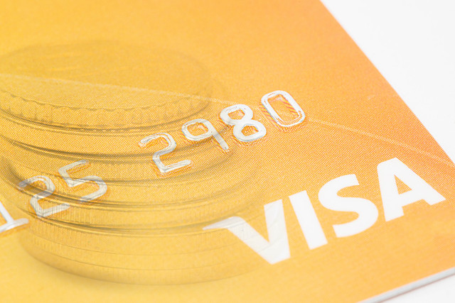 Visa credit card with coins in the background concept with copy space