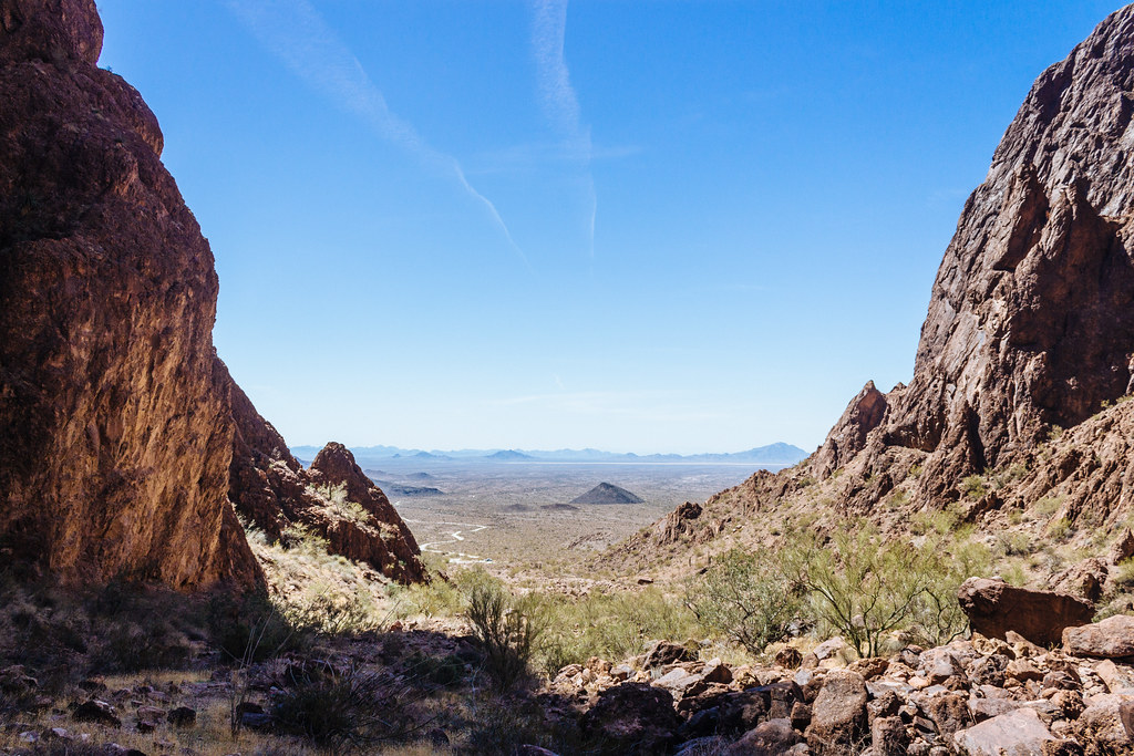Steep canyon walls open up onto a flat desert landscape on a cloudless day