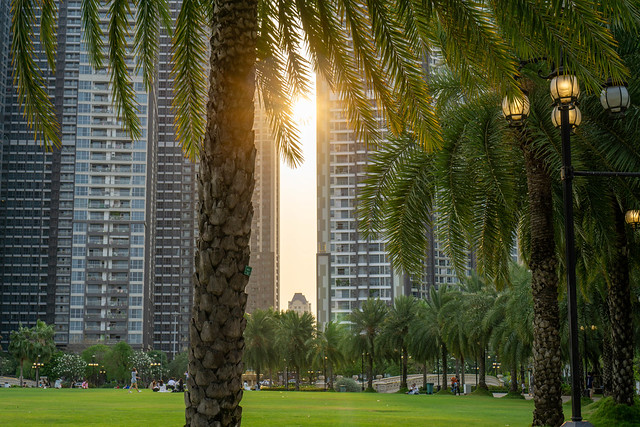 Sunset behind Vinhomes Apartment Buildings at Vinhomes Central Park with Palm Trees and Big Lawn in Ho Chi Minh City, Vietnam