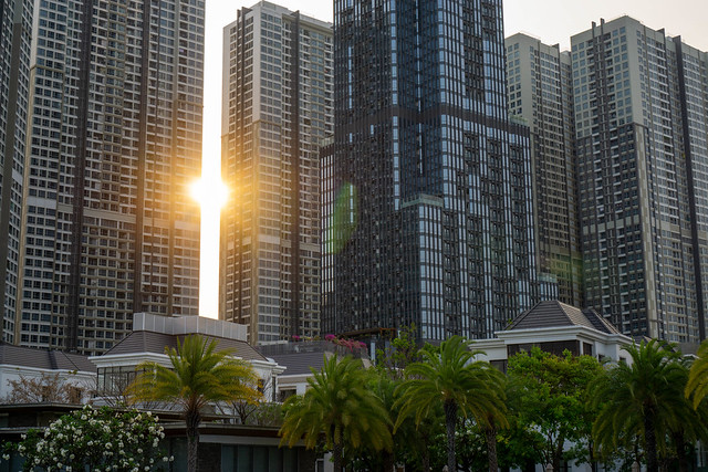 Sunset behind Vinhomes Apartment Buildings and Vincom Landmark 81 Skyscraper with Villas in the Foreground in Saigon, Vietnam