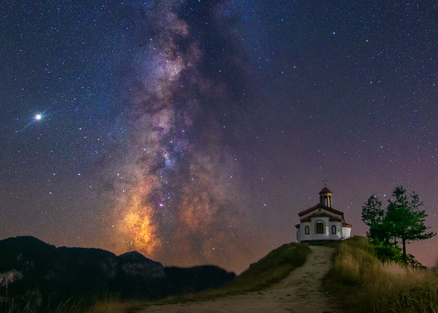 A chapel in the Rhodope Mountain at midnight and the magnificent night sky