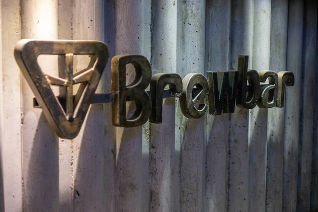 Brewbar Steel Brand Logo with Letters on a Cafe Wall with Lamps pointing on it