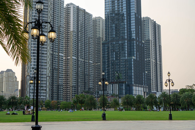 People on Large Lawn of Vinhomes Central Park with Vinhomes Apartment Buildings and Vincom Landmark 81 Building at Sunset in Ho Chi Minh City, Vietnam