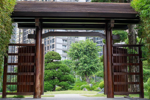 Wooden Arch in Japanese Style as a Gate of a Garden with Fish Pond and Flowers within Vinhomes Central Park in Binh Thanh District of Saigon, Vietnam