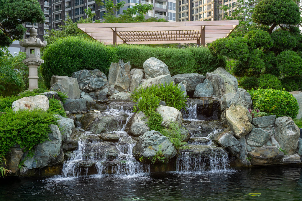 Small Waterfall with Rocks and Flowers into a Fish Pond with Koi Fish at Vinhomes Central Park in Ho Chi Minh City, Vietnam