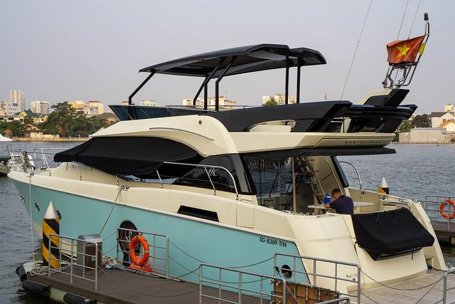 Private Yacht mit Sonnendeck und Vietnamesischer Flagge im Privat-Hafen von Vinhomes Central Park und Apartments in Ho Chi Minh Stadt, Vietnam