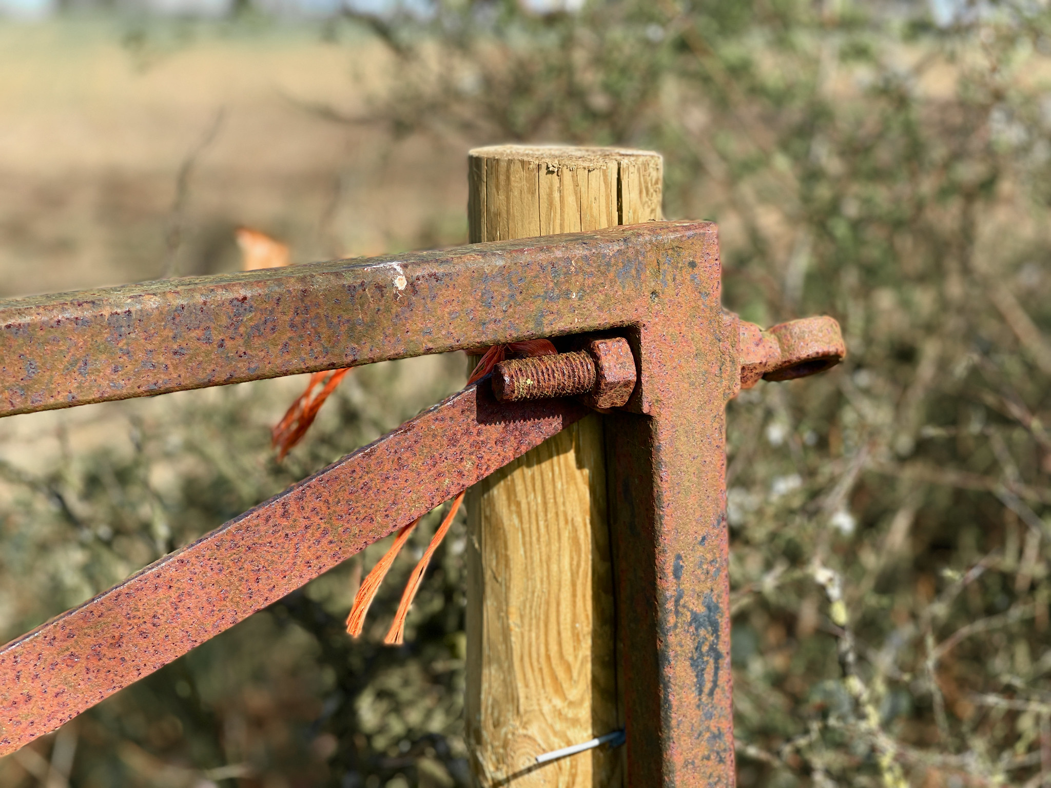 Gate leaning against post held with baler twine