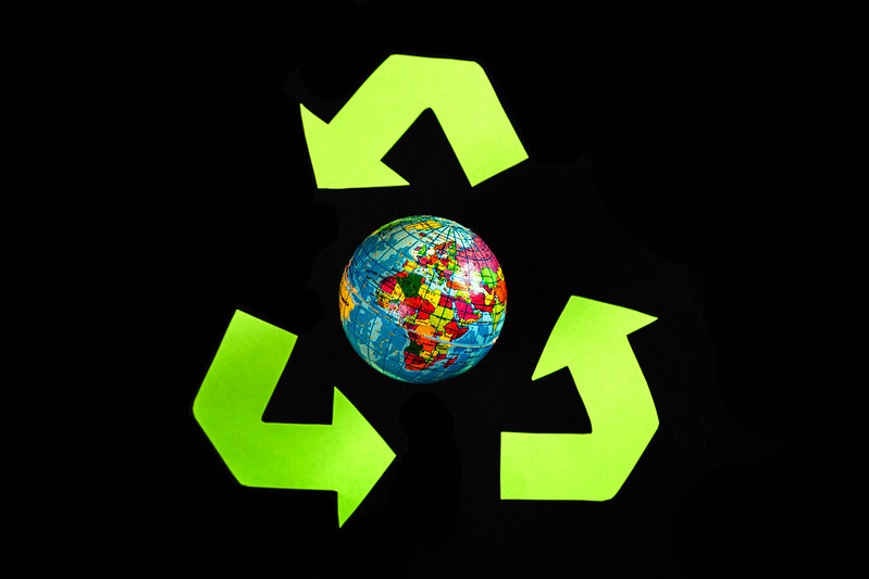 Green recycle eco symbol and globe on dark background