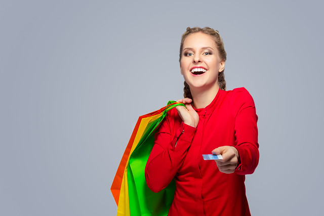 Shopping Concepts. Portrait of Laughing Caucasian Blond Girl With Bunch of Colorful Shopping Bags Showing Bank Card Towards.