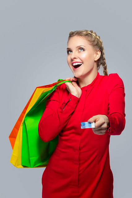 Modern Shopping Concepts. Portrait of Exclaiming Caucasian Blond Girl With Bunch of Colorful Shopping Bags Showing Bank Card Towards.