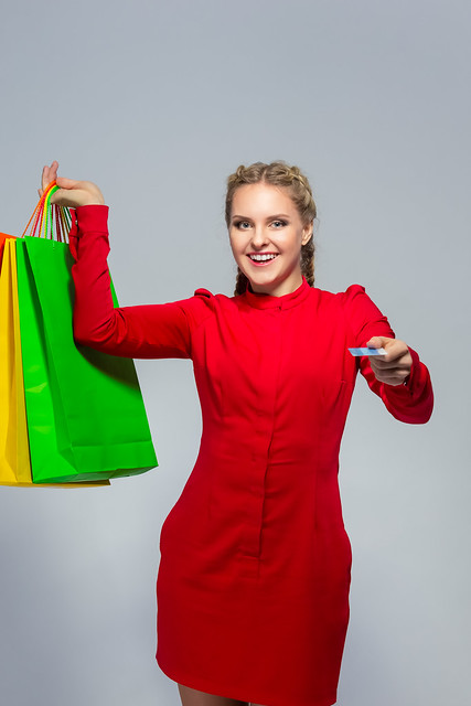 Modern Shopping Concepts.Positive Caucasian Girl With Bunch of Colorful Shopping Bags Showing Bank Card Towards.