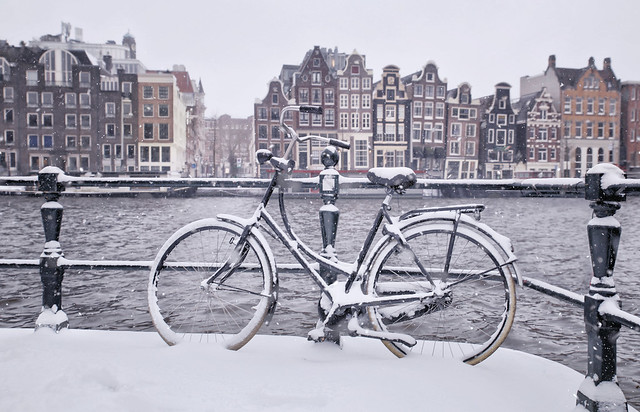 Bicycle under snow at Amstel river in Amsterdam