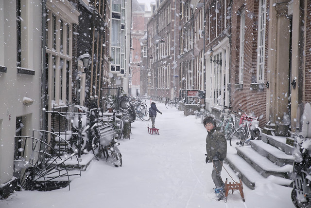 Snow flakes falling while kids sledding in the Spinhuissteeg - Amsterdam