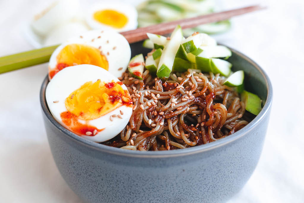 A side shot of bibimmyeon noodles with cucumbers and eggs