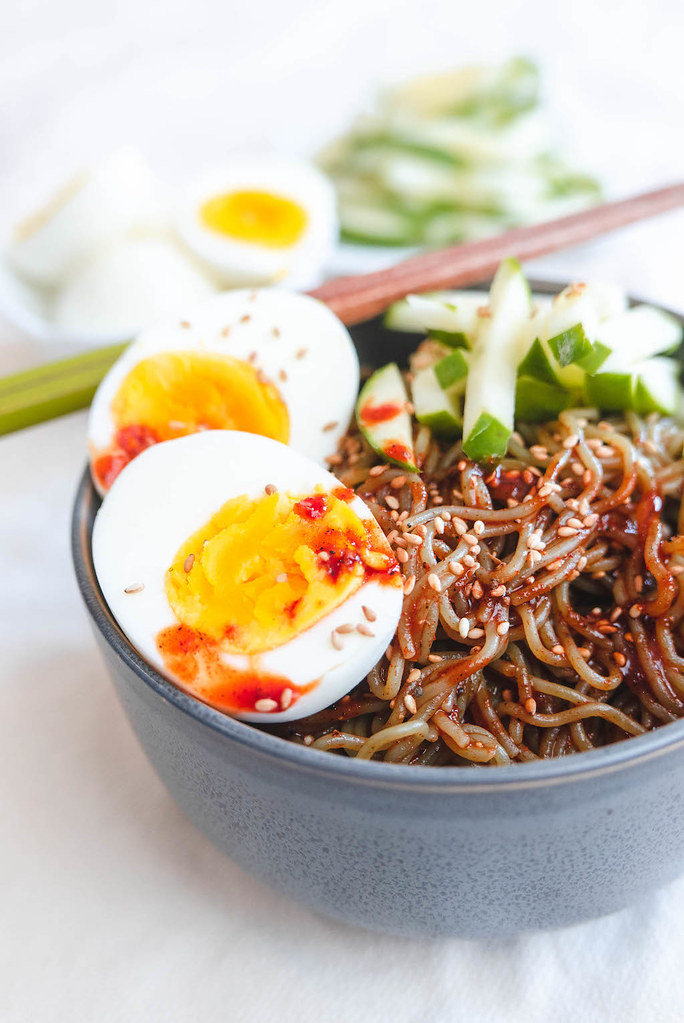 A side shot of bibimmyeon, eggs, and cucumbers.