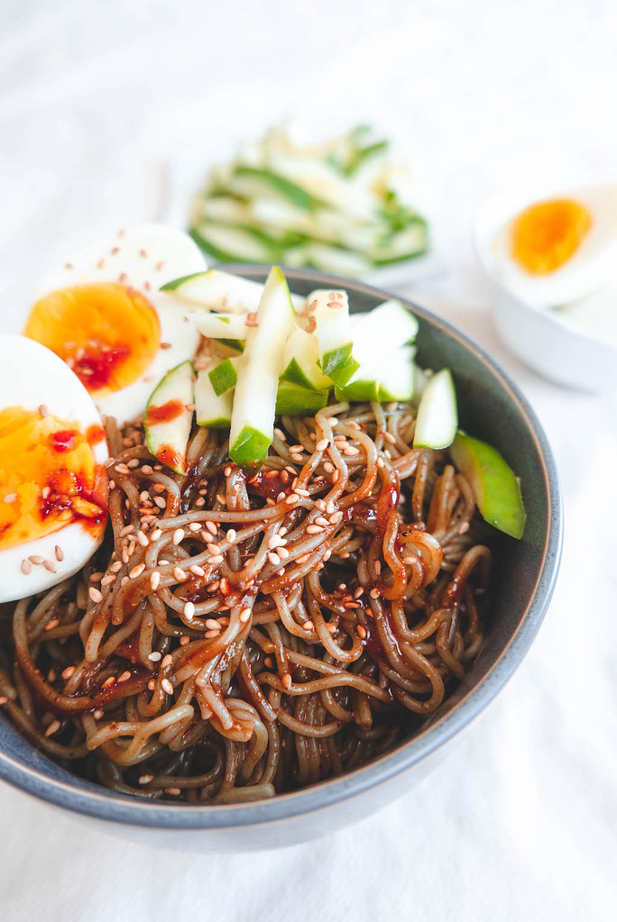 An overhead shot of spicy red noodles, cucumbers, and eggs.