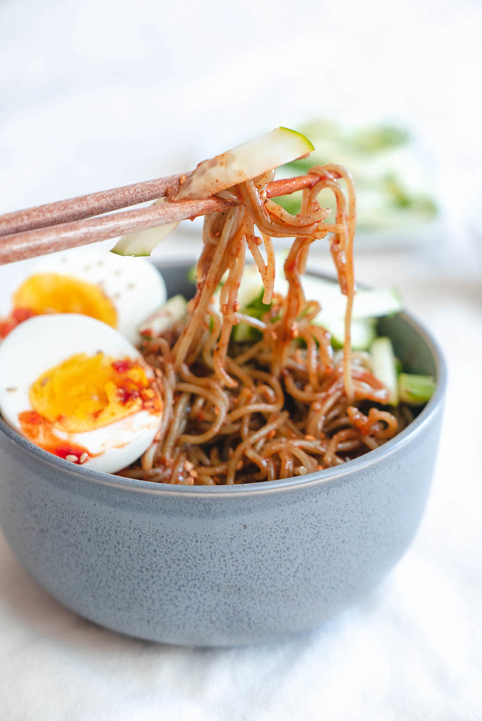A side shot of bibimmyeon with chopsticks, eggs, and cucumbers.