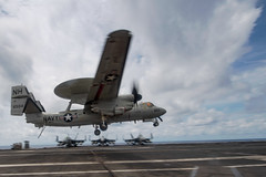 """SOUTH CHINA SEA (April 5, 2021) An E-2C Hawkeye assigned to the """"Liberty Bells"""" of Airborne Command and Control Squadron (VAW) 115) lands on the flight deck of the aircraft carrier USS Theodore Roosevelt (CVN 71). The Theodore Roosevelt Carrier Strike Group is on a scheduled deployment to the U.S. 7th Fleet area of operations. As the U.S. Navy's largest forward-deployed fleet, 7th Fleet routinely operates and interacts with 35 maritime nations while conducting missions to preserve and protect a free and open Indo-Pacific Region. (U.S. Navy photo by Mass Communication Seaman Faith McCollum)"""