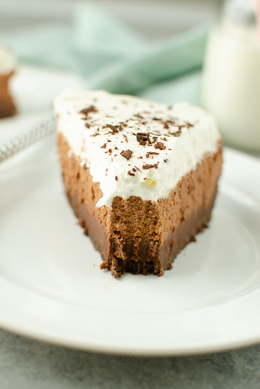 Slice of chocolate layer pie topped with whipped cream and chocolate shavings; a bite taken out of the pie