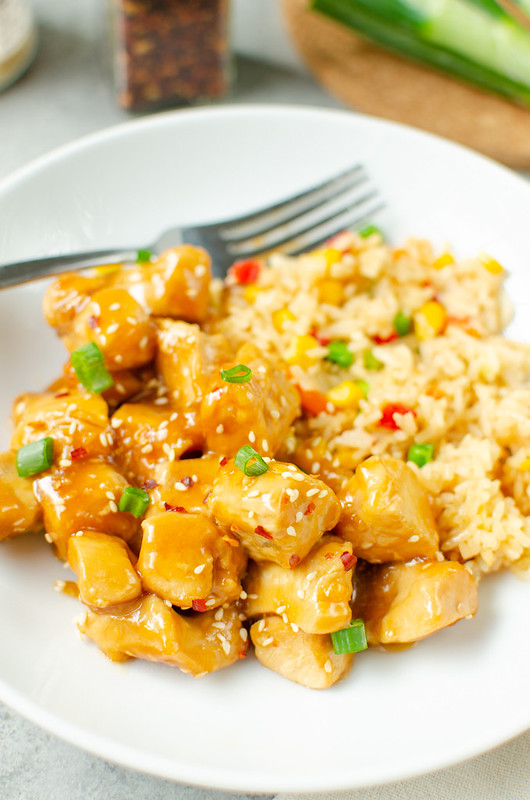 Chicken pieces in a sweet honey and soy sauce, topped with sesame seeds, green onions, and crushed red pepper flakes. Served with fried rice on a white plate.