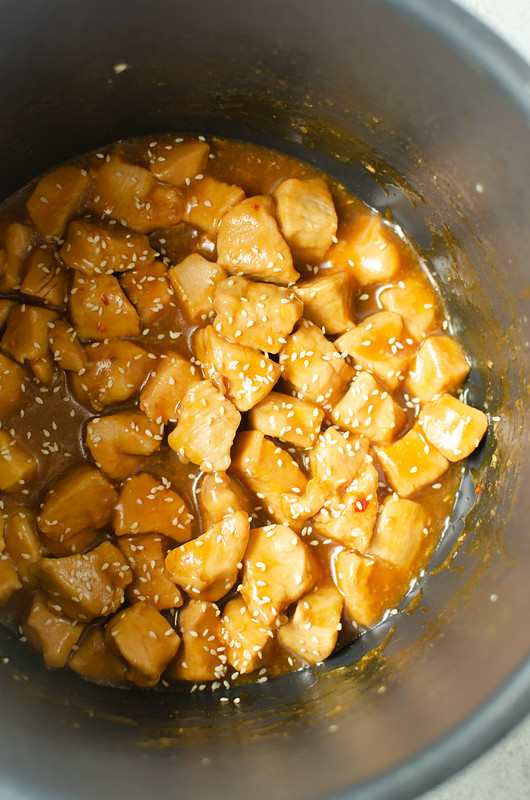 Chunks of chicken in sesame sauce and sprinkled with sesame seeds in a pressure cooker
