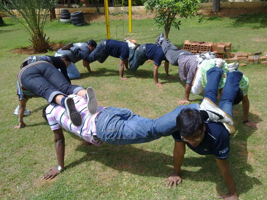 a circle of 9 human beings engaged in a team-building activity. Each person has two hands on the grass and their two feet on the shoulders of the person behind them. Towards the back of the circle the people don't have enough space to do this and rather have their knees on the floor instead