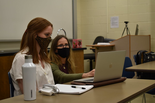 Jamie Harrison and Emily Johnson look at a laptop.