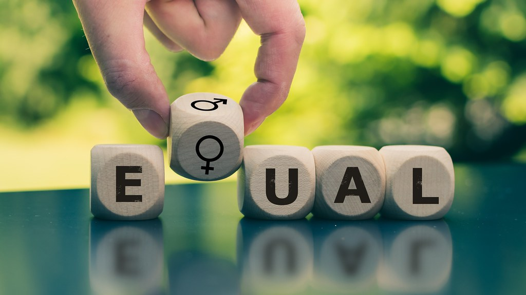 A hand placing a dice with a female symbol into a row on dice spelling out the word equal