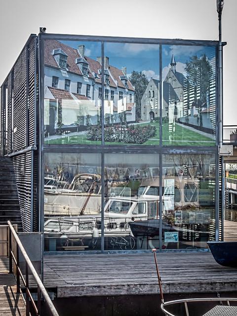 Reflectie van boot in ruit gebouw.