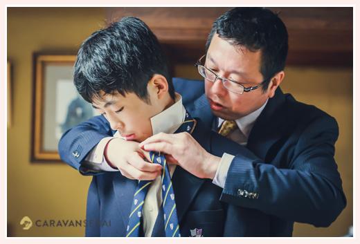 パパにネクタイの結び方を教えてもらう高校生の男の子