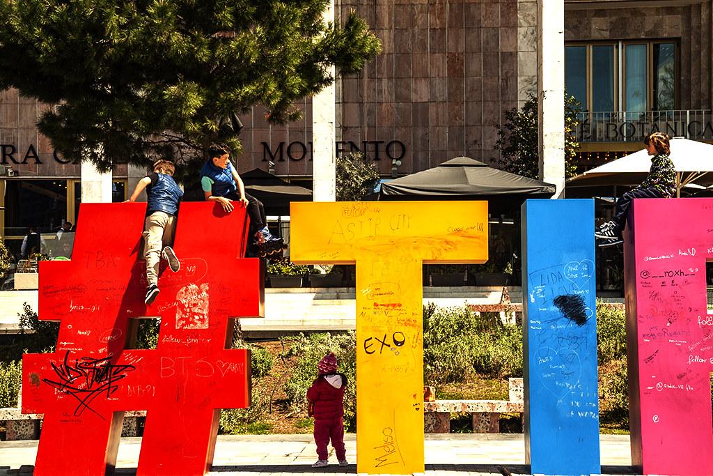 Boys climbing on giant hashtag and letters at Skanderbeg Square on 4-8-21--Tirana