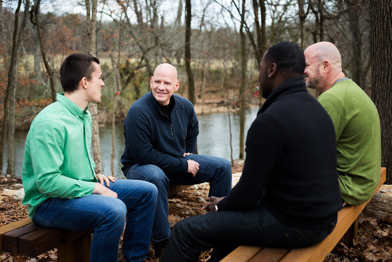 Men Sitting Talking by River Outdoors