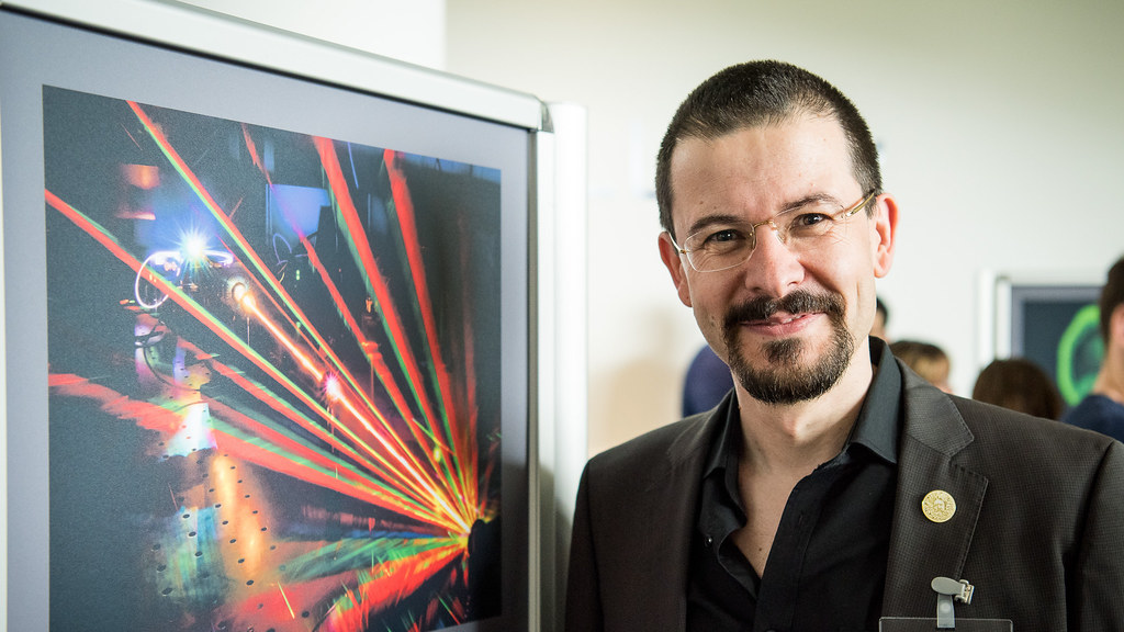 Academic smiling next to image of his work