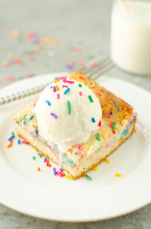 Funfetti gooey butter cake with vanilla ice cream and sprinkles on top; on a white plate with a fork and a glass of milk in the background