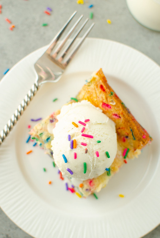 Overhead shot of funfetti gooey butter cake with vanilla ice cream and sprinkles on top; on a white plate with a fork and a glass of milk in the background