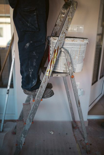 Closeup of worker´s legs on the ladder during house reconstruction.