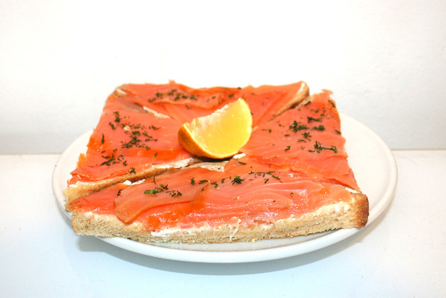 Smoked salmon with cream cheese on toast - Side view / Räucherlachs mit Frischkäse auf Toast - Seitenansicht