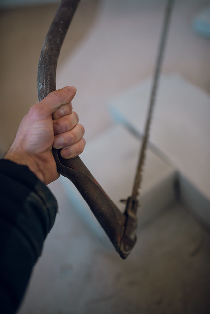 A man holding old hand saw.