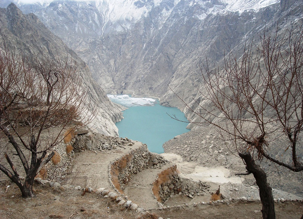 Attabad Lake in Pakistan is light blue in the middle of the image. Mountains rise steeply around the lake, leafless trees are in the foreground along with some sculpted curved steps cut into the rock