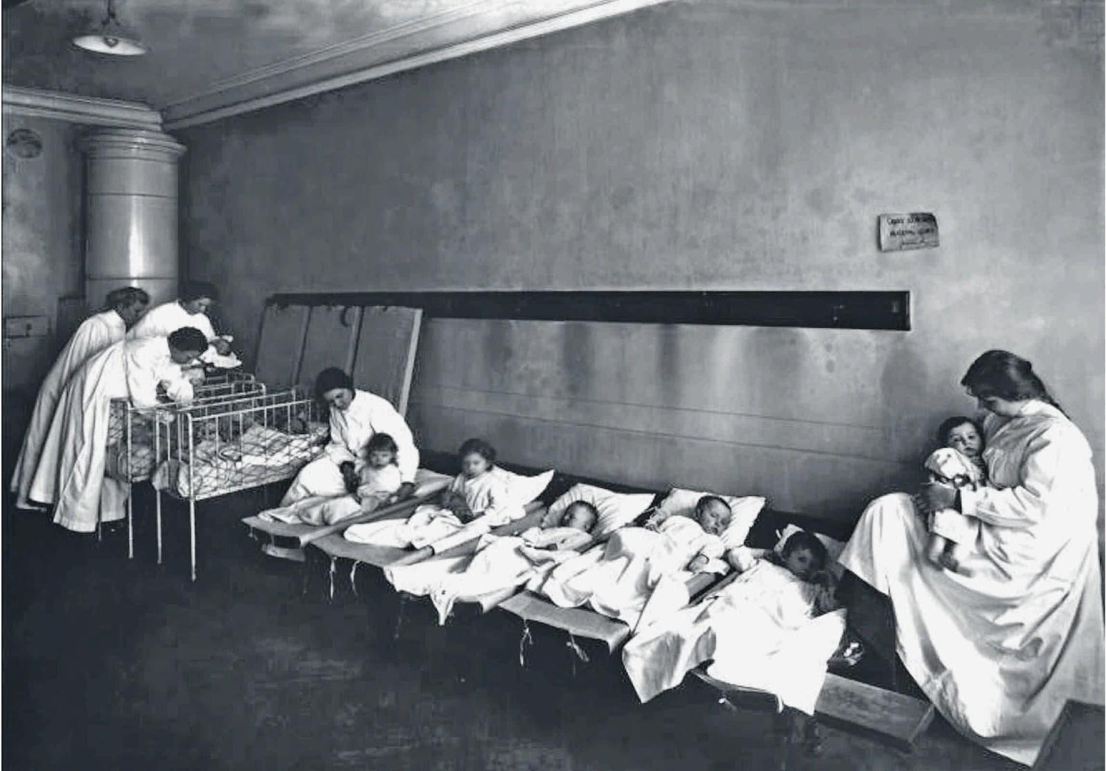 88. 1910-е. Детская больница принца Ольденбургского. Учащиеся женского училища принцессы Терезии Ольденбургской укладывают детей спать
