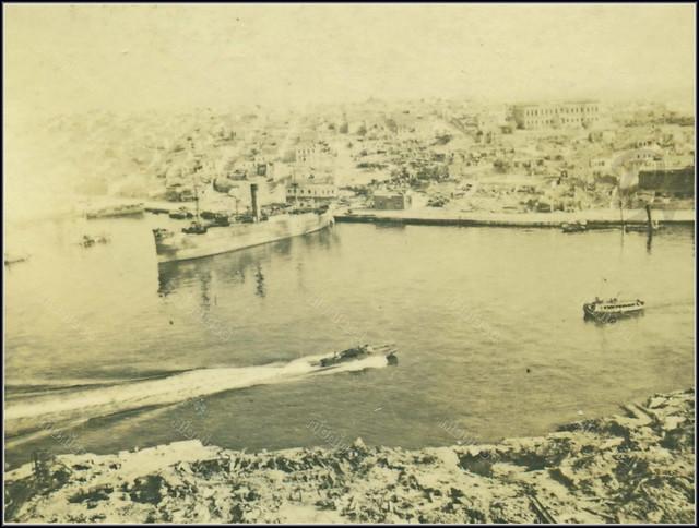 Πειραιάς, 1941. Η ακτή Ξαβερίου μετά τους γερμανικούς βομβαρδισμούς, δεξιά πάνω το Χατζηκυριάκειο Ορφανοτροφείο Θηλέων.