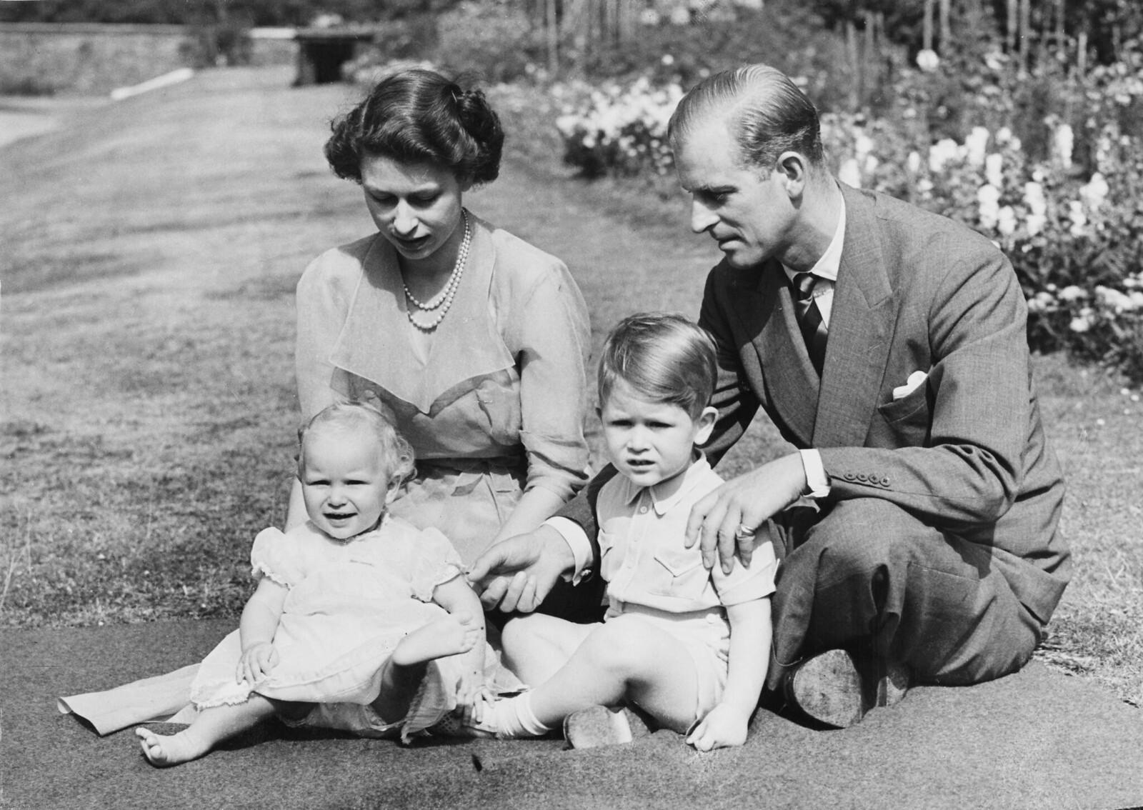 21. Принцесса Елизавета и принц Филипп, герцог Эдинбургский, сидят с принцем Чарльзом и принцессой Анной на территории Кларенс-хаус