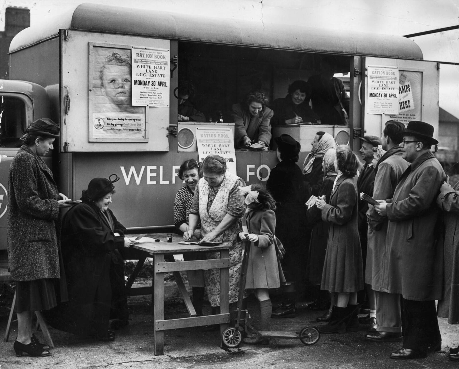 07. Мисс Магуайр из продовольственного отдела Тоттенхэма (за столом) раздает карточки на продовольственные товары местным домохозяйкам из нового мобильного офиса, припаркованного на Уайт-Харт-лейн в Лондоне