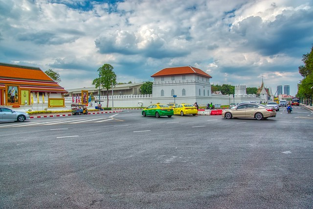 Traffic near Wat Pho and Grand Palace under a cloudy sky in Bangkok, Thailand